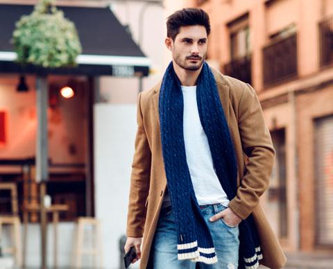 Mann i frakk og blått skjerf med hånden i lommen