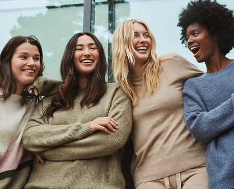 Fire kvinner smiler til kamera