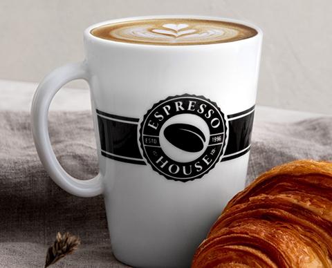 Espresso house kopp med kaffe  og en croissant