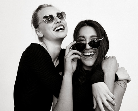 To jenter som smiler og har på seg solbriller.