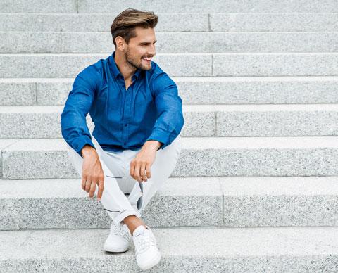 Mann sittende i trapp med blå skjorte og lyse chinos