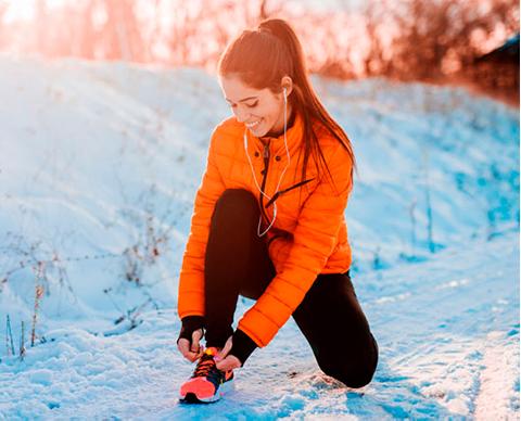 Kvinne i oransje jakke knyter løpesko