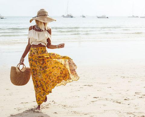 Kvinne på strand med hvit topp og gult skjørt
