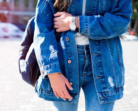Bilde av en jente med olajakke og jeans.
