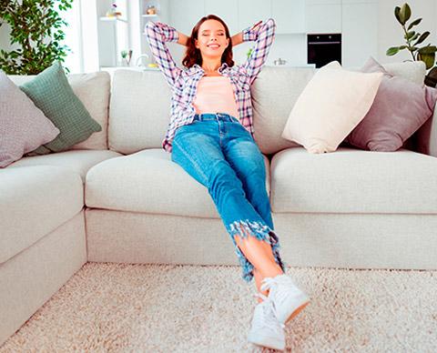 Dame som slapper av på sofaen